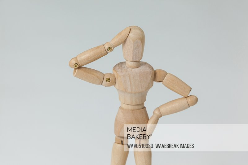 Confused wooden figurine standing with hand on head against white background