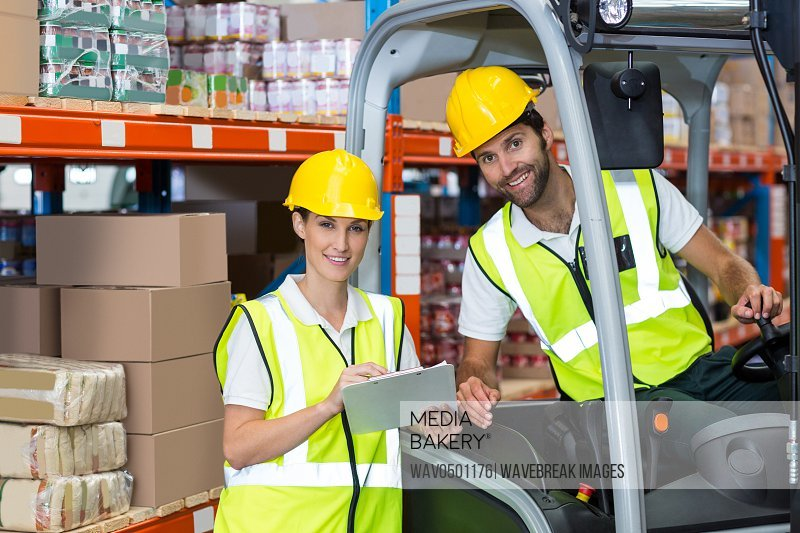 Male and female worker discussing over clipboard in warehouse
