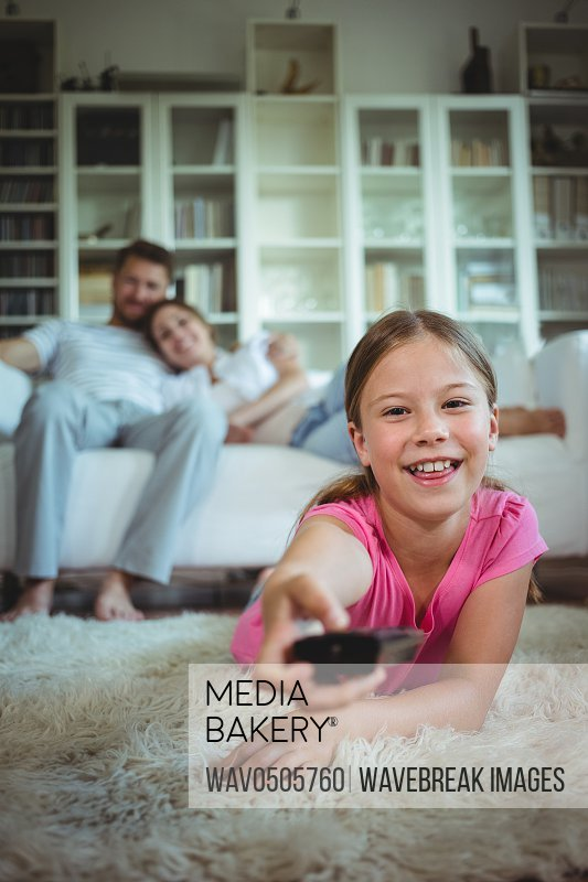 Smiling girl lying on rug and changing channels at home