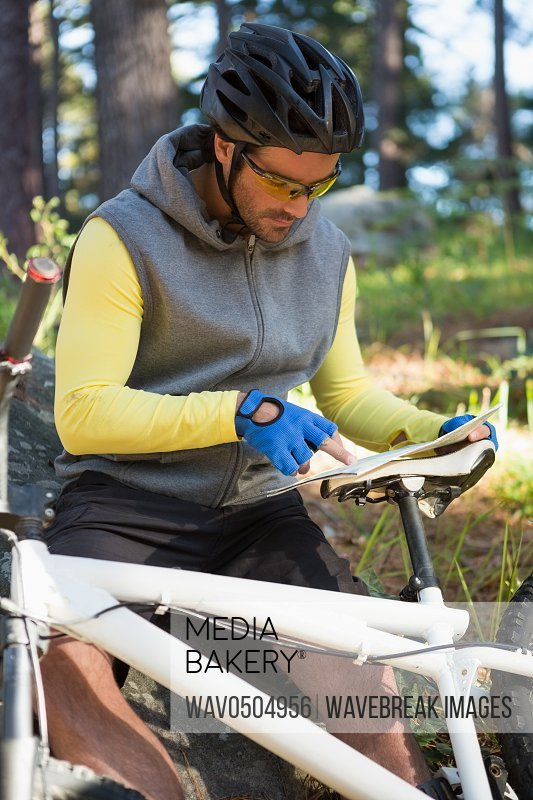 Mountain biker looking at map in the forest