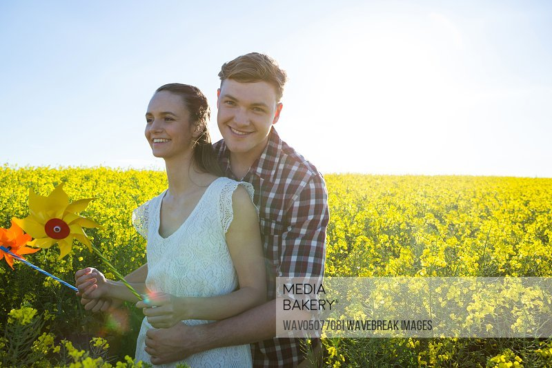 Couple holding pinwheel and embracing each other in mustard field on a sunny day