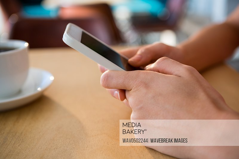 Close-up of hands using a mobile phone in coffee shop