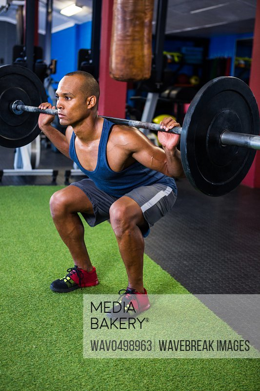 Full length of young man weightlifting in gym