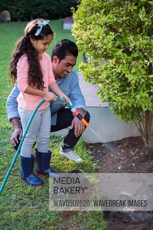 Father and daughter spraying water to plant in garden at backyard