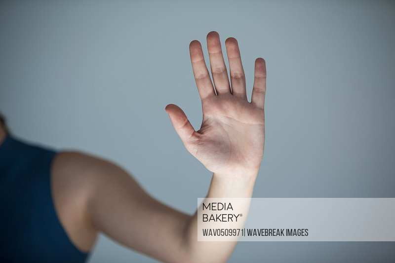 Hand of a woman touching an invisible screen against grey background