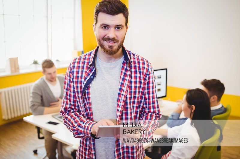 Portrait of happy confident young businessman with tablet at creative office
