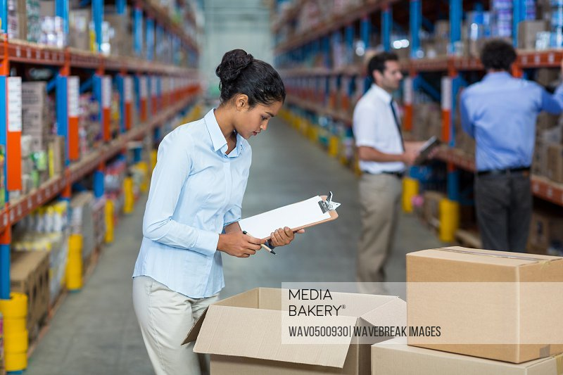 Female warehouse worker with a clipboard checking the boxes in the warehouse