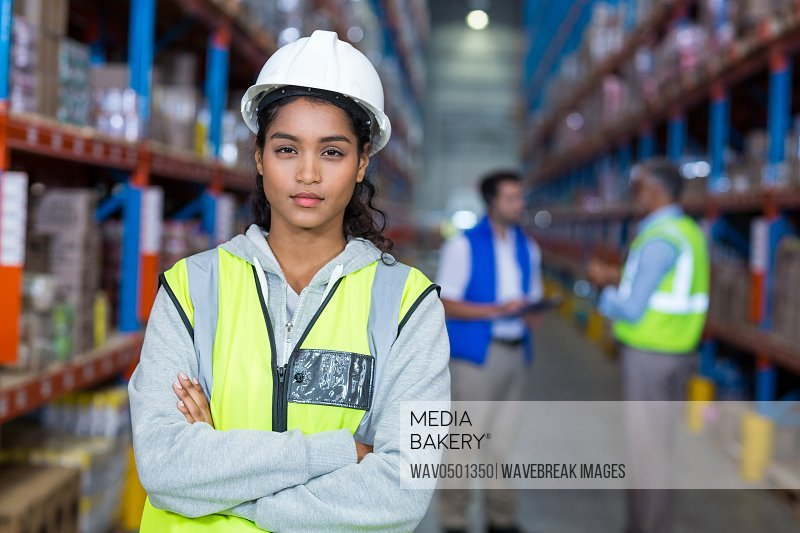 Portrait of female warehouse manager standing with arms crossed in warehouse