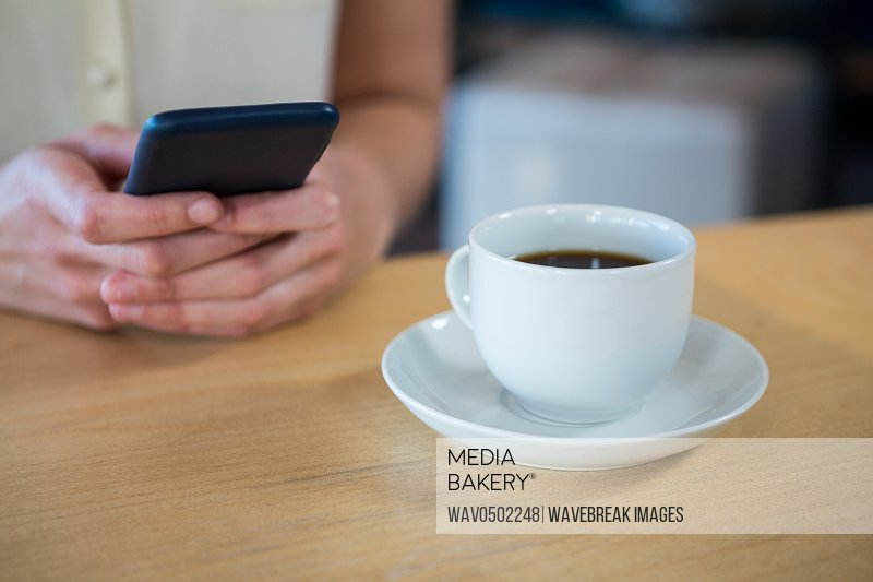 Mid section of woman using mobile phone and a coffee cup on the table in coffee shop