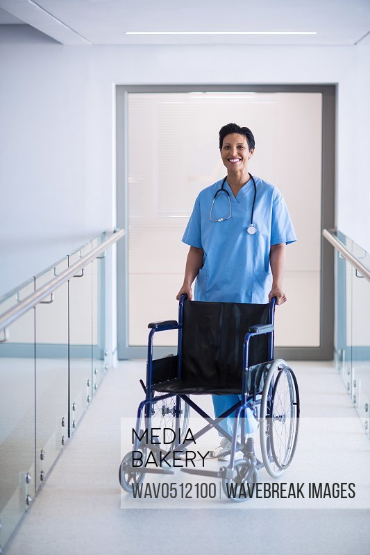 Portrait of female nurse standing with wheelchair in corridor of hospital