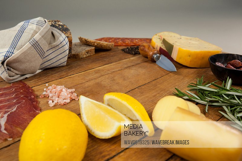 Cheese ham lemon and bread with various ingredients on chopping board