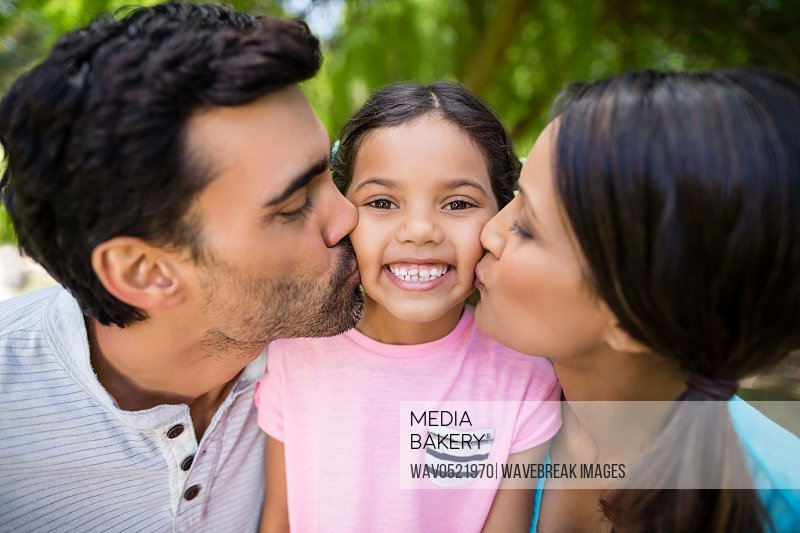 Girl being kissed by his parents in park