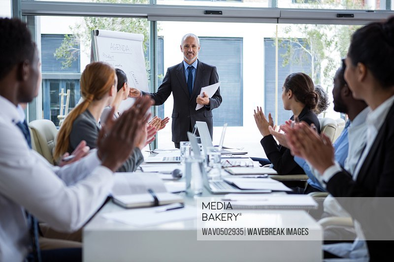 Businesspeople applauding on their colleagues presentation in office