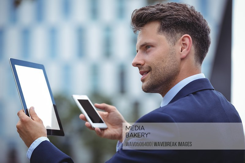 Happy businessman using digital tablet and mobile phone