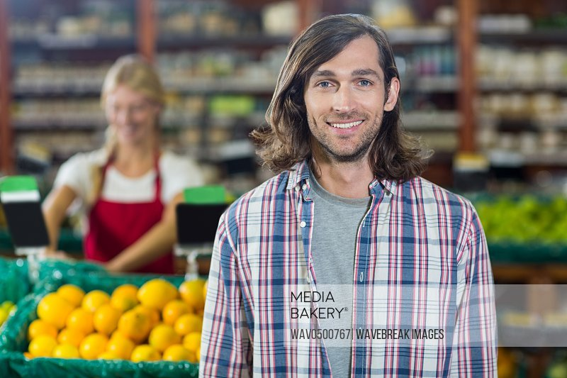 Portrait of smiling man standing in organic section of supermarket