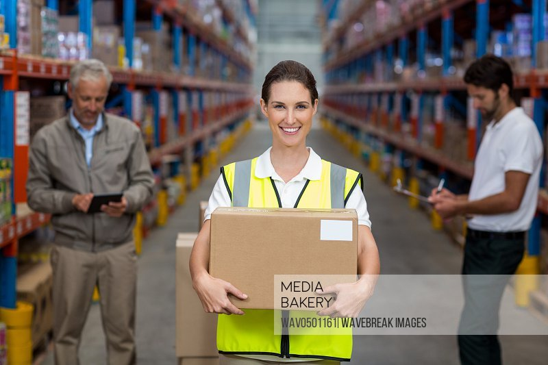 Female worker holding cardboxes while colleague working in background at warehouse