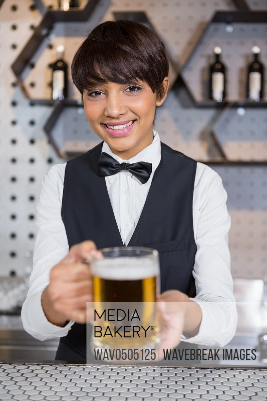 Barmaid serving glass of beer at bar counter in bar