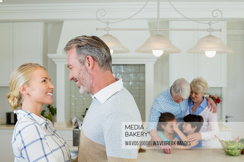 Romantic couple looking face to face at kitchen