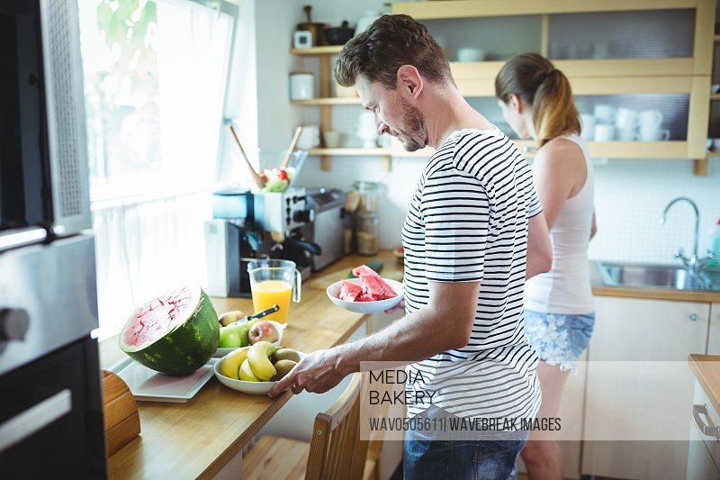 Couple preparing breakfast with fruits in kitchen