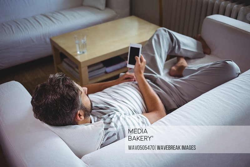 Man using his mobile phone in living room at home