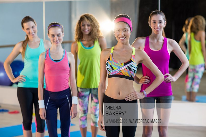 Group of women standing with hands on hips in gym