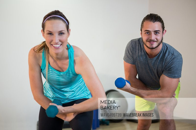 Portrait of man and woman doing aerobic exercise with dumbbell in fitness studio