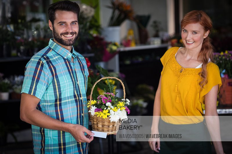 Female florist and customer with flower basket and visiting card in the flower shop