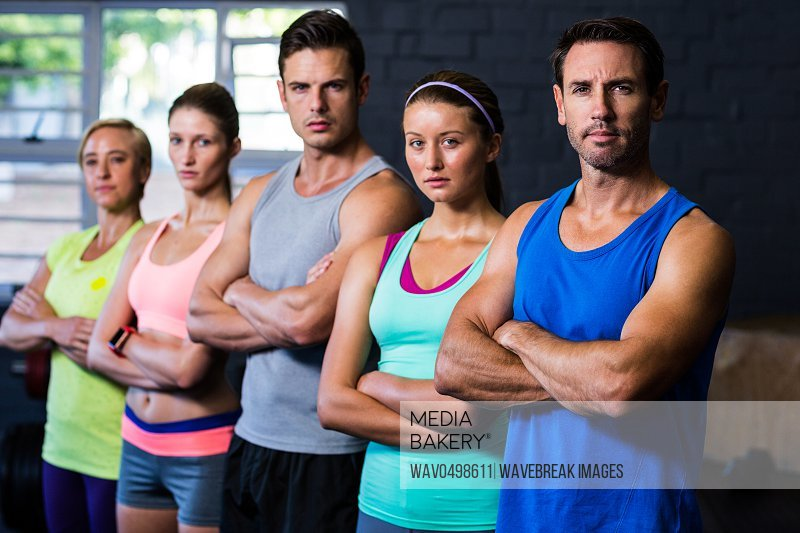 Portrait of confident male and female athletes with arms crossed standing in gym
