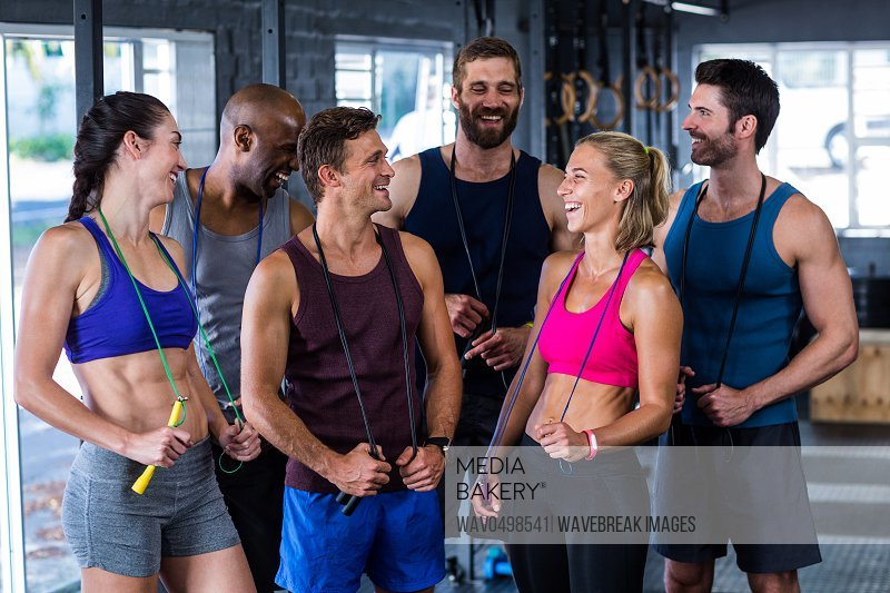 Smiling friends with jumping ropes while standing in gym