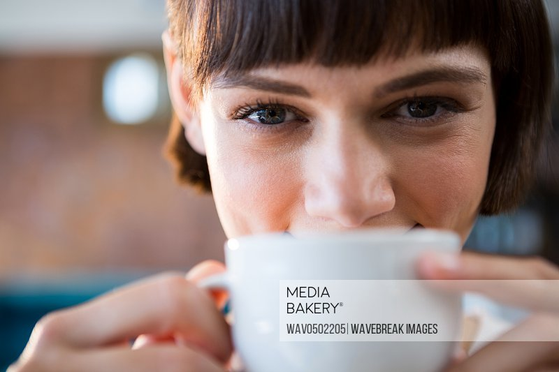 Portrait of smiling woman having cup of coffee in cafeteria