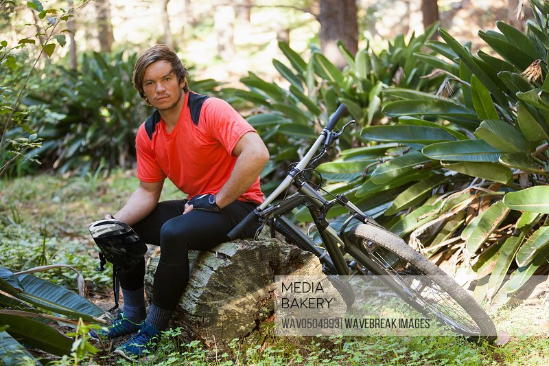 Portrait of exhausted male mountain biker relaxing on a tree trunk in the forest