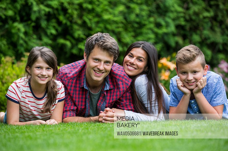 Portrait of happy family lying in park on a sunny day