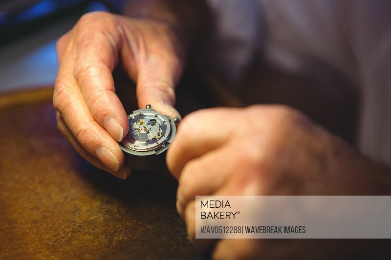 Horologist examining a clock part in workshop