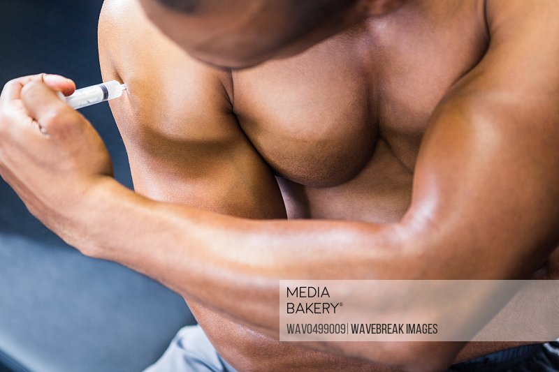Midsection of muscular man injecting steroid on arm