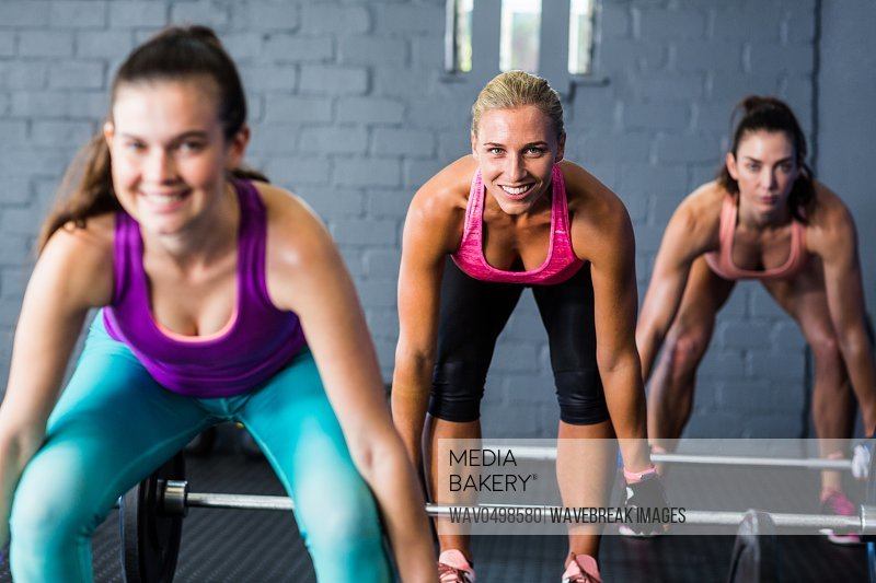 Portrait of smiling female athletes lifting barbells in gym