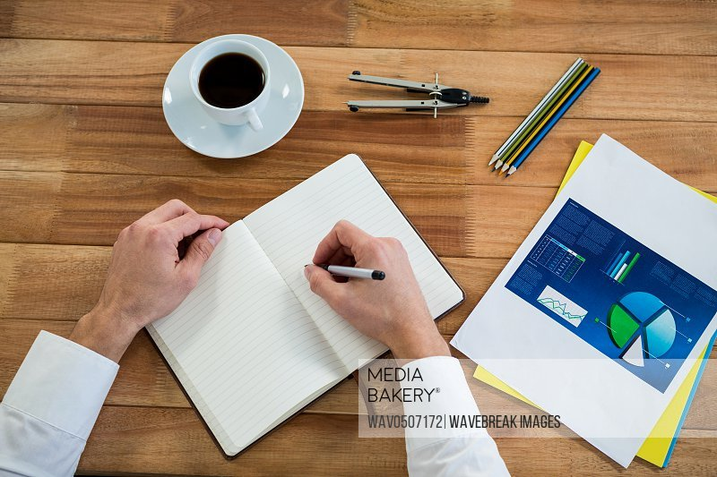 Businessman writing on a diary in office