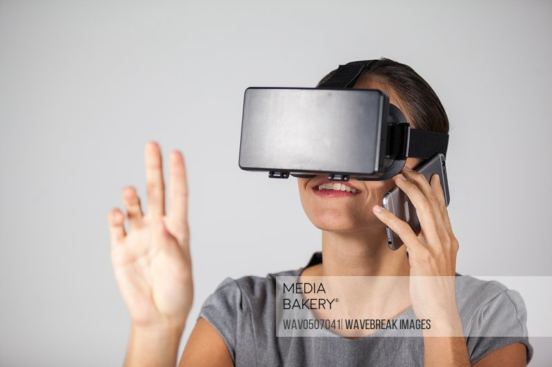 Woman talking on mobile phone while using virtual reality headset against white background