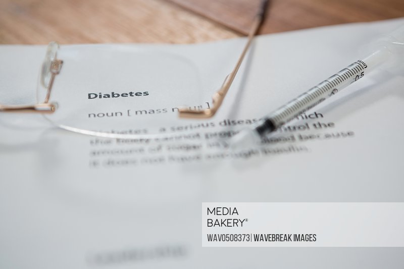 Close-up of injection with diabetes test paper and spectacle on table