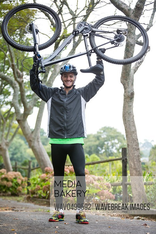 Portrait of male cyclist carrying mountain bike in park