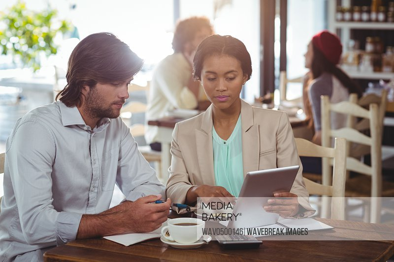 Man and woman using a digital tablet during meeting in restaurant