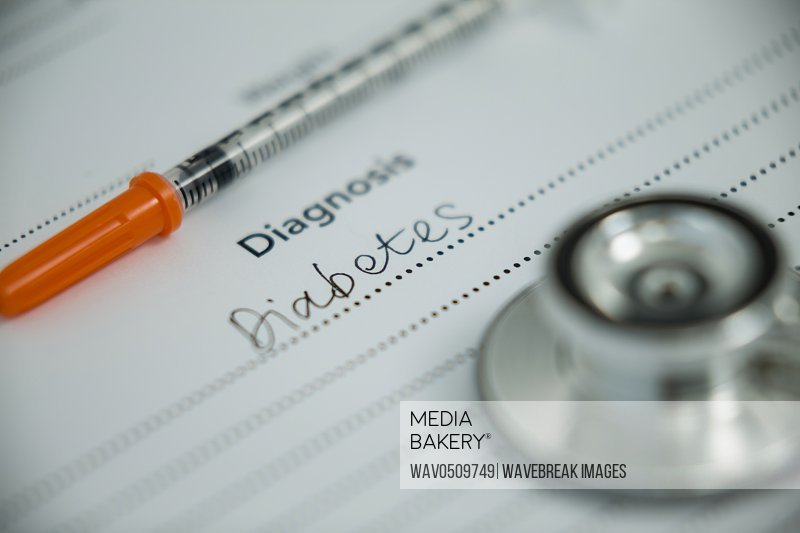 Close-up of injection with diabetes diagnosis and stethoscope