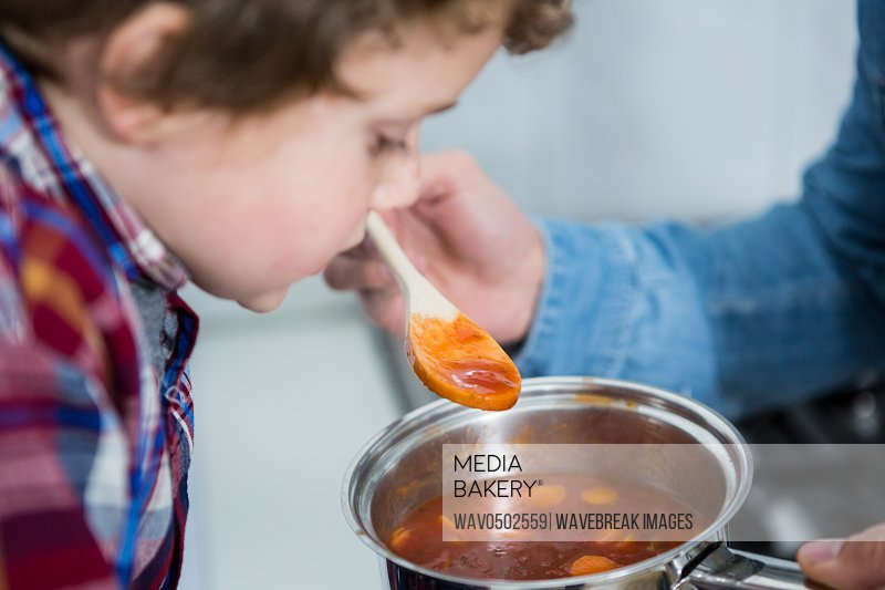Close-up of son tasting food in the kitchen