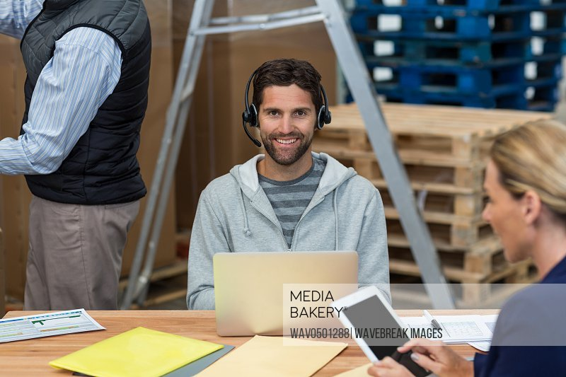 Portrait of smiling man using laptop in warehouse