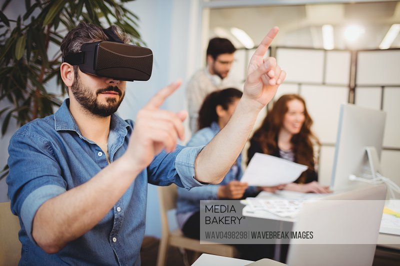 Creative businessman gesturing while using virtual reality headset against coworkers