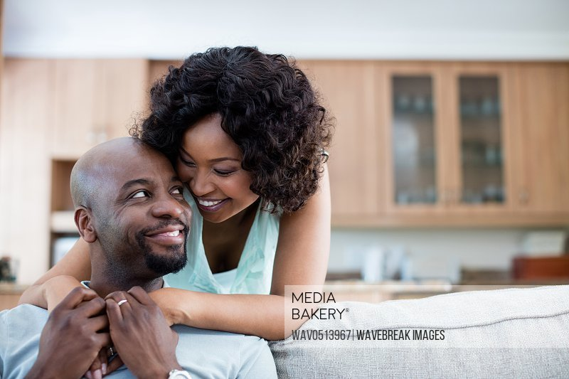 Smiling couple embracing each other in living room