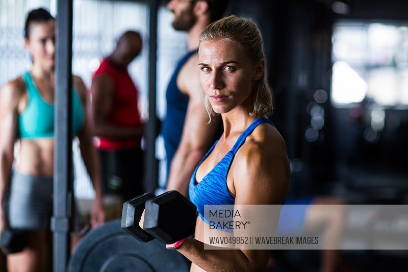 Portrait of serious woman holding dumbbell while standing in gym