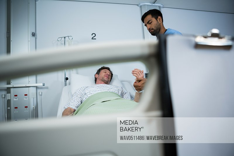 Doctor checking pulse of patient in hospital