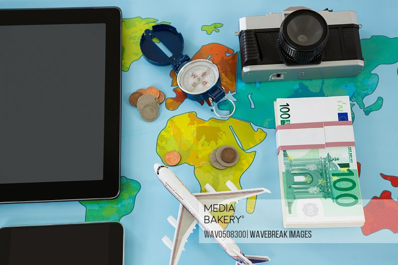 Electronic gadgets camera dollar compass and airplane model on table