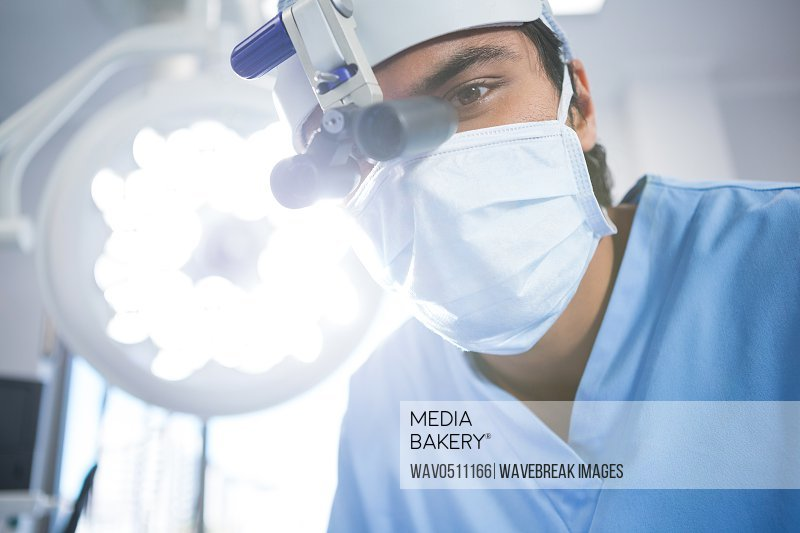 Male surgeon wearing surgical loupes in operation theater