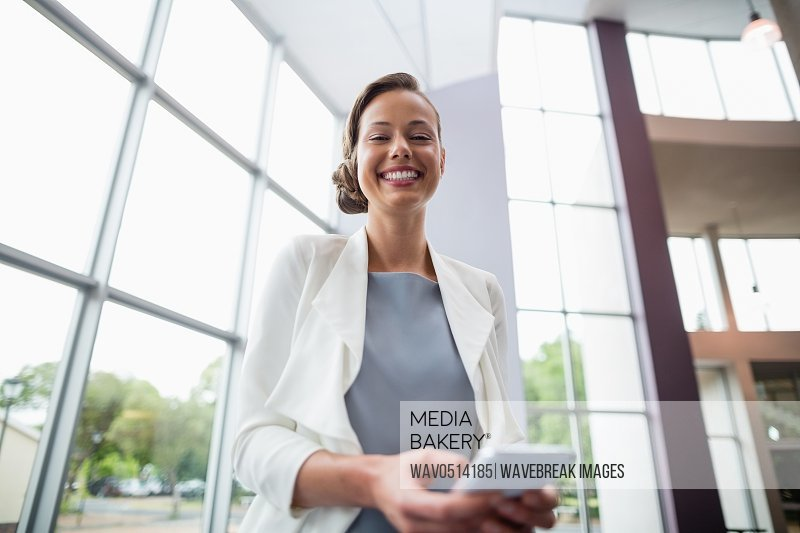 Cheerful businesswoman holding mobile phone
